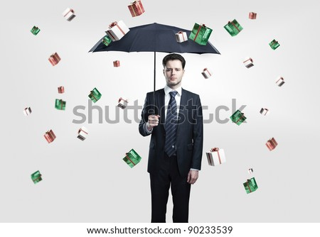 Young Business man with umbrella under gift boxes rain. On a gray background. - stock photo