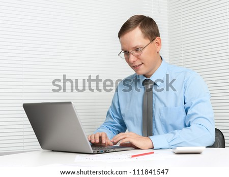 young business man working on computer at office desk - stock photo