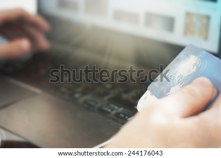 Young business man working on laptop with credit card - stock photo