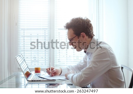 young business man working with documents and laptop in bright office interior - stock photo