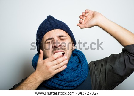 young business man yawning, winter style clothes, studio shot isolated on the gray background - stock photo