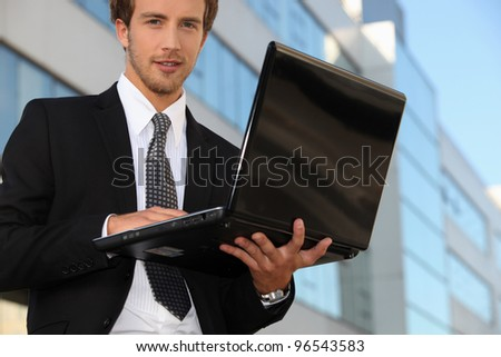 Young business outside office with laptop computer - stock photo