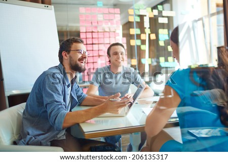 Young business partners sharing and discussing ideas at meeting in office - stock photo