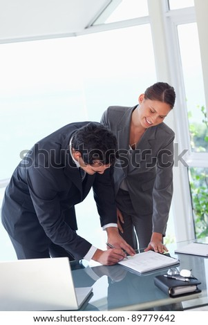 Young business partners signing contract - stock photo