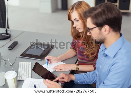 Young business partners working in the office sitting together at a desk using a tablet computer, man and woman with focus to the woman - stock photo