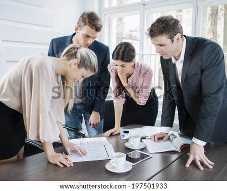Young business people brainstorming at conference table in office - stock photo
