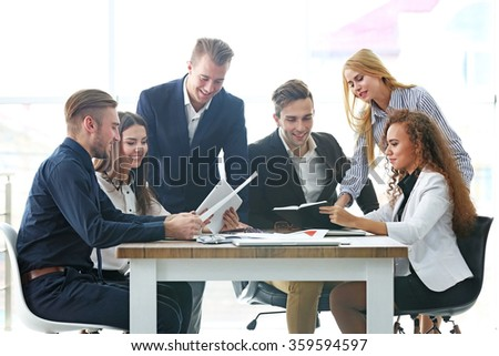 Young business people discussing a new project at the meeting in office - stock photo
