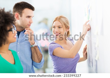 Young business people discussing on adhesive notes - stock photo