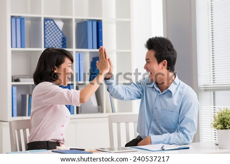 Young business people giving high five a symbol of success - stock photo