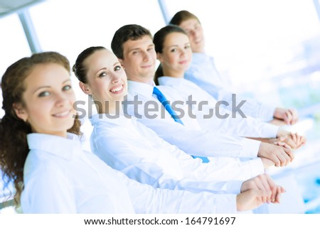 young business people holding hands, standing in a row, the concept of teamwork - stock photo