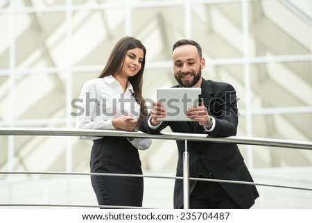 Young business people in modern office is looking at the tablet. - stock photo