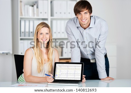 young business people presenting chart on laptop - stock photo