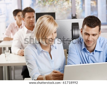 Young business people sitting at desk, using computer at business training, smiling.? - stock photo