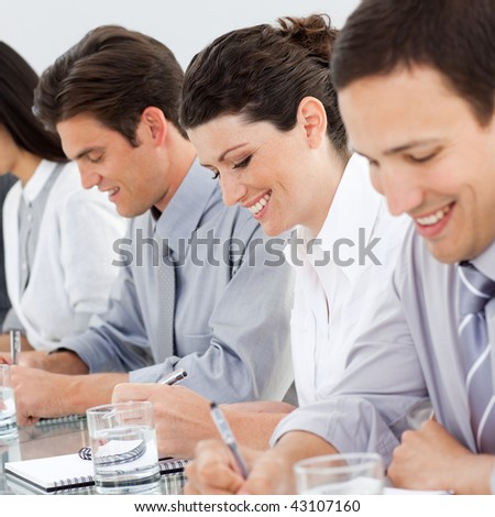 Young business people taking notes at a conference in the office - stock photo
