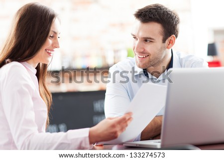 Young business people using laptop at cafe - stock photo
