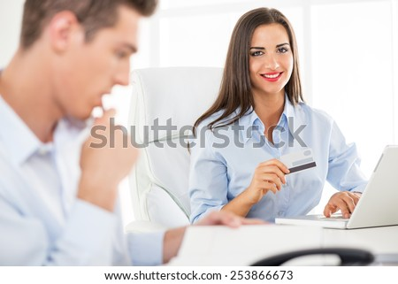 Young business people, woman and man, sitting in an office, a young businesswoman which is in the foreground holding a credit card and with a smile looking at the camera. - stock photo