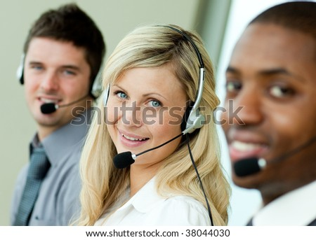 Young business people working in the office with headsets - stock photo