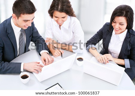 Young business people working on laptop in modern office - stock photo