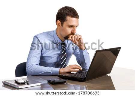 Young business person at office desk looking on laptop / businessman in shirt and tie, gazes wistfully into the laptop - isolated on white background  - stock photo