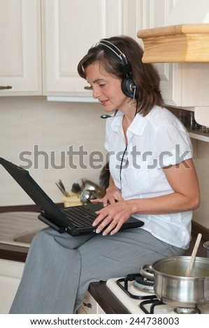 Young business person with headset working from home on laptop while cooking meal in kitchen - stock photo