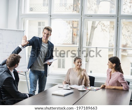 Young business team enjoying success at conference table - stock photo