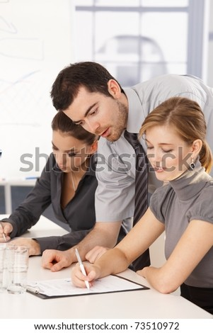Young business team having training, sitting at meeting table. - stock photo