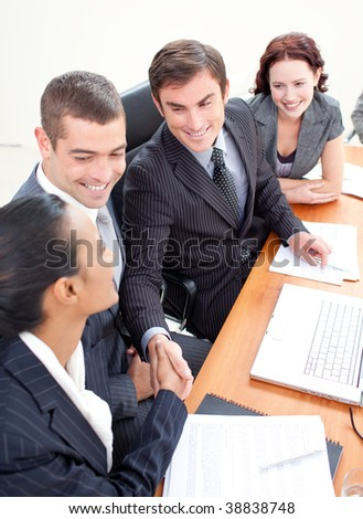 Young business team in a meeting shaking hands - stock photo