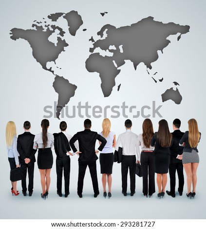 Young business team looking at world map - stock photo