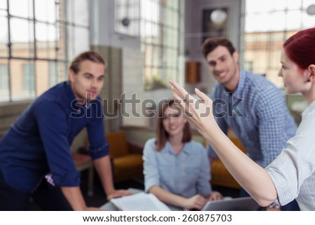 Young business team of diverse men and women listening to their team leader as she explains a point gesturing with her hand, focus to her arm and side of her face - stock photo
