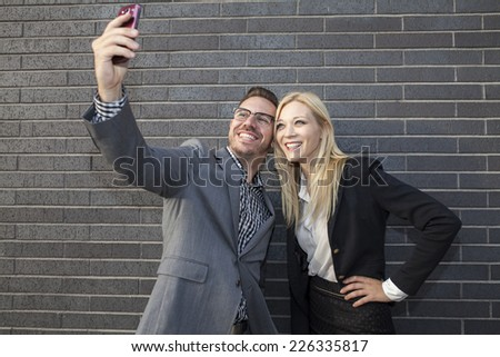 Young business team outdoors in urban setting taking a selfie - stock photo