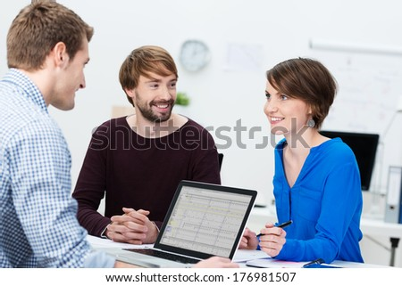 Young business team with an attractive woman and two men sitting around a desk and laptop computer having a brainstorming session - stock photo