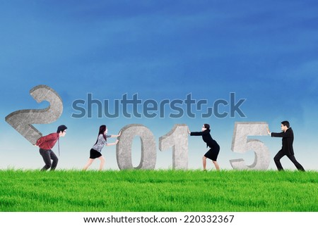Young business teamwork composing number 2015 on the meadow - stock photo