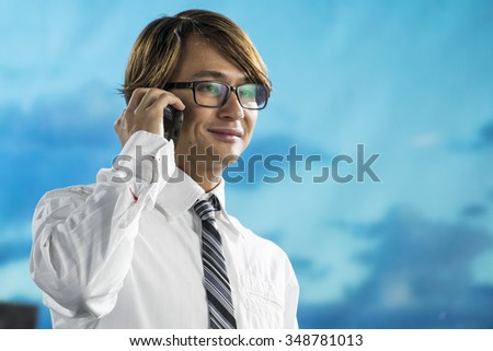 Young business traveler talking on cellphone at the airport, close up shot - stock photo