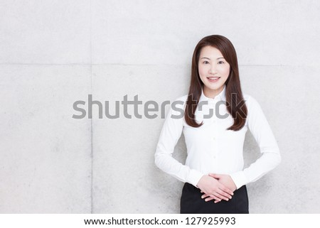 young business woman against concrete wall - stock photo