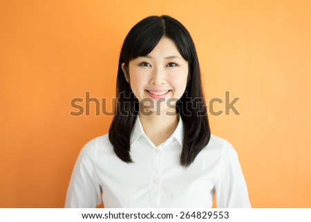 young business woman against orange background - stock photo