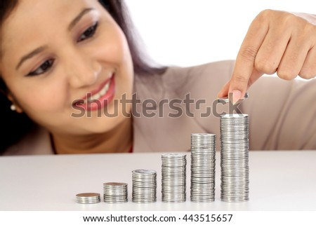 Young business woman arranging stack of coins - Money growth concept - stock photo