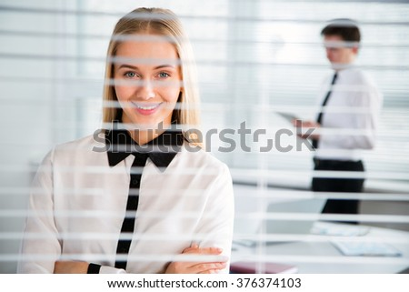 Young business woman at the office blinds. - stock photo