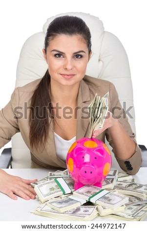 Young business woman at the table with a lot of money and moneybox, isolated on white background. - stock photo