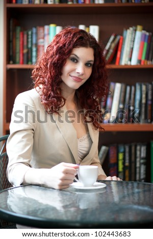 Young business woman at work in an office having a cup of coffee - stock photo