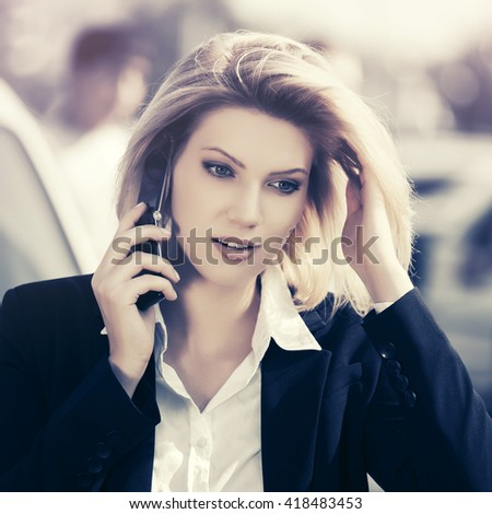 Young business woman calling on cell phone outdoor. Female fashion model in black jacket on city street - stock photo