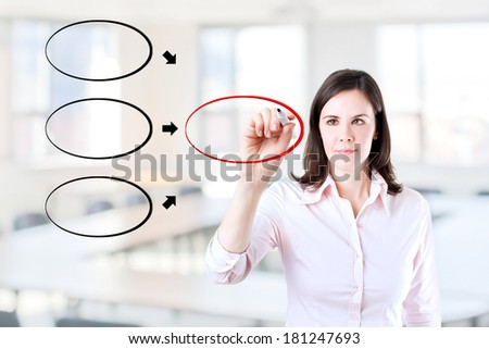 Young business woman drawing diagram on whiteboard. Office background. - stock photo