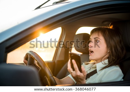 Young business woman drives car with mobile phone in hand - risky driving - stock photo