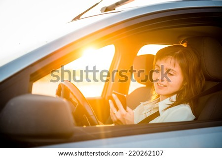 Young business woman driving car and looking simultaneously in her mobile phone - stock photo