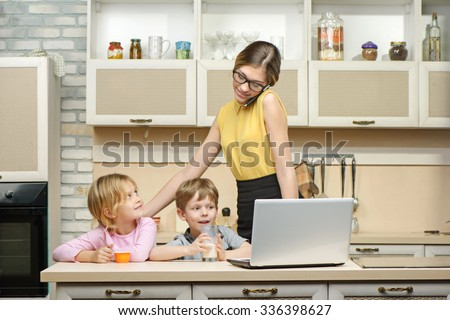 Young business woman early in the morning with her little children. She using laptop and phone. Kitchen interior. Concept for busy mother - stock photo