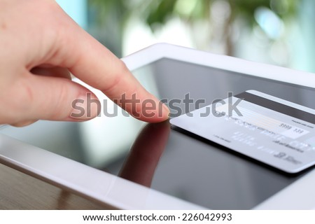 Young business woman entering data from the credit card . On-line shopping on the internet using a tablet  - stock photo