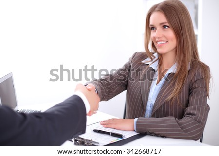 young business woman handshaking  sitting at the desk on office background, copy space area at the left upper corner - stock photo