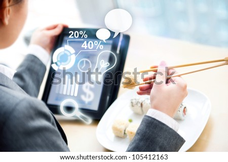 Young business woman having a business lunch at cafe with free wifi internet. She is looking at report of her company using her tablet computer - stock photo