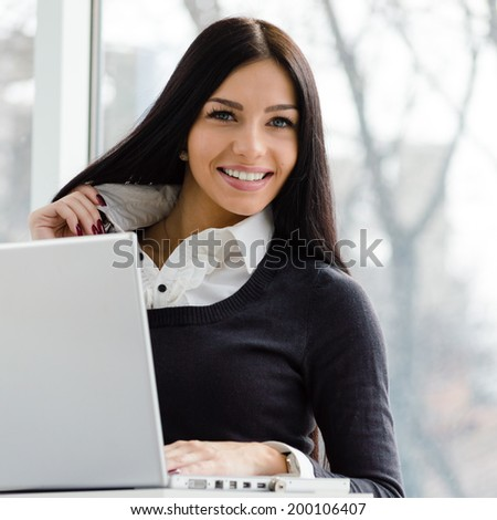 young business woman having fun using laptop PC computer at office desk happy smiling & looking at camera on light window copy space background portrait image - stock photo