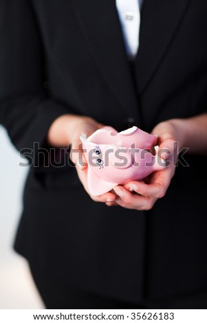 Young Business woman holding a broken piggy bank - stock photo