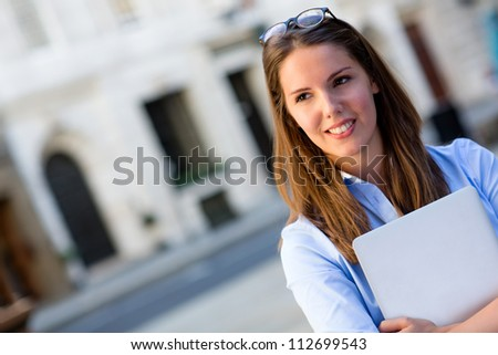 Young business woman holding a laptop computer - stock photo